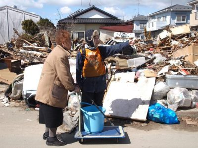 A Peace Boat volunteer helps in the aftermath of the earthquake/tsunami; photo by Jon Mitchell