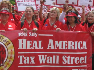 Nurses display a banner calling for a tax on Wall Street. Photo by Sarah Anderson