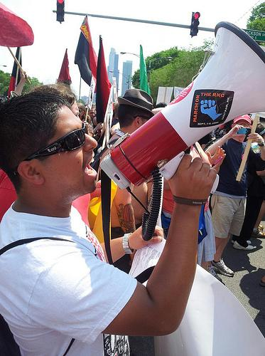 A demonstrator leads chants outside the NATO summit in Chicago. [Photo by brads651/Flickr]