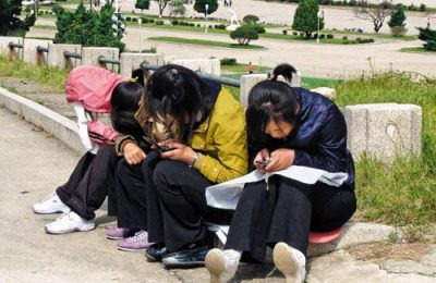 North Korean girls use their cell phones in a park.