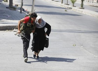 A Free Syrian Army fighter helps a woman run across a street during clashes in Aleppo. Photo by Goran Tomasevic.