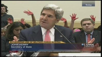 Code Pink holds up bloody hands behind Secretary of State John Kerry throughout two-hour hearing.