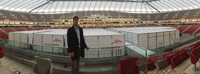 Robbie Watt in front of COP19's plenary session boxes, sponsored by the corporation ArcelorMittal