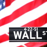 Wall Street sign with the American flag draping the columns of the New York Stock Exchange