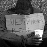 Homeless man holding sign 'Very Hungry Please'