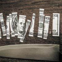 Dollar bill being cut up