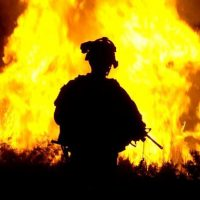 Solider with fire in the background