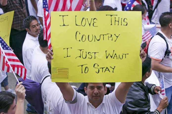 "Man holding sign at an immigration rally reading ""I love this country, I just want to stay"""