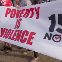 "workers strike holding sign ""poverty is violence - $15 now"""