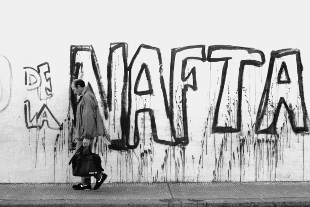 man in nikes in front of NAFTA graffiti