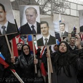 Syrians hold photos of Syrian President Bashar Assad and Russian