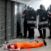 Prison guards stand over prisoner on the ground
