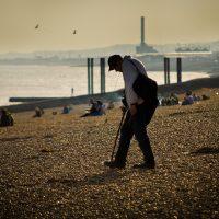man walks along beach in destination town
