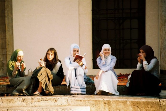 women-hijab-reading-eating-sidewalk